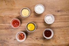 套调味汁-番茄酱、蛋黄酱、芥末酱油、bbq调味汁、芥末五谷和石榴在木桌上调味 图库摄影