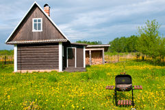 After the BBQ. Summer log house on a meadow with a BBQ in front Royalty Free Stock Image