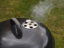 BBQ. Photograph of a Bar-b-q, with smoke coming from the vent Stock Image