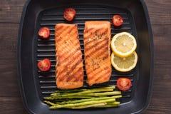 烤三文鱼烹调了在一个平底锅的BBQ在木背景 库存照片