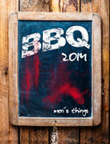 BBQ advertised on an old vintage school slate. In a grunge wooden frame on a rustic table with an addendum at the bottom saying - Mans stuff Royalty Free Stock Photos