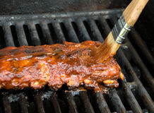 BBQ Baby Back Ribs. Cooking on the grill with BBQ sauce being applied with a brush Stock Images