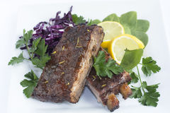 BBQ Baby Back Ribs. Smoked Barbecue Baby Back Ribs decorated with Spinach Red Cabbage Lemon and Parsley in a White Ceramic Plate Stock Photography