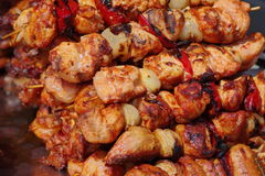 BBQ barbecuing skewers kebab close up. Close up of BBQ barbecuing skewers kebab, coal grill of chicken meat skewers with onion and peppers stock image