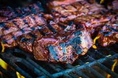 BBQ Beef Ribs on Hot Grill. Boneless beef ribs grilling over flames with added barbecue sauce. Extreme shallow depth of field with blurred background with focus royalty free stock photography
