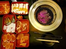 BBQ buffet on the table. BBQ buffet consist of meats, shrimp, squid, chicken, pork on a black table Stock Photos