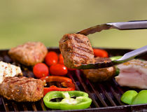 BBQ with burgers, pappers, tomatos and mushrooms Stock Photos