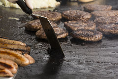 BBQ 1. Burgers and Sausages being cooked on a gas operated plate on August 20th, 2016 at Portrush , Northern Ireland Royalty Free Stock Photography