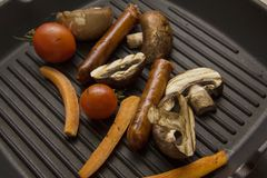 Bbq with carrots and tomatoes. Chicken legs and wings on a grill pan Royalty Free Stock Photography