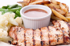 Bbq chicken breast with fries, jus and vegetables Stock Photo