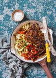 BBQ chicken and grilled vegetables in a cast iron skillet on a dark background, top view. Stock Image