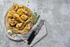 BBQ chicken legs on the tray with the Kraft paper. Gray background, top view, space for text. royalty free stock images