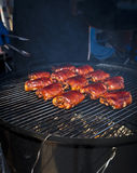 BBQ. Chicken thighs on a smoker royalty free stock images