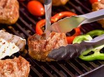 Bbq con las hamburguesas, los pappers, los tomates y las setas Fotos de archivo