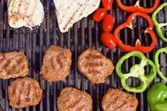 Bbq con las hamburguesas, los pappers, los tomates y las setas Imagen de archivo