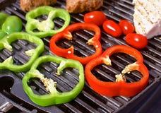 Bbq con las hamburguesas, los pappers, los tomates y las setas Imagenes de archivo