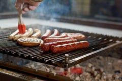 BBQ con le salsiccie sulla griglia Fotografia Stock