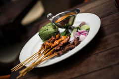 BBQ cooked skewers of chicken and beef with satay sauce. Delicious BBQ cooked skewers of chicken and beef with satay sauce and rice wrapped in leaves Stock Photos