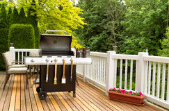 BBQ cooker and cookware ready to cook. Photo of a clean barbecue cooker with cookware and cold beer in bucket on cedar wood patio. Table and colorful trees in stock images