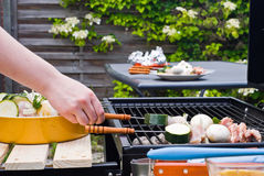 BBQ Cooking. Placing the material on a grate above the coal stock image