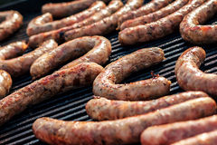BBQ with fiery sausages on the grill. Red baked delicious juicy sausages in row. Tasty sausage preparing on a barbecue grill. Royalty Free Stock Photos