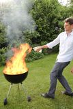 BBQ with fire an young man Royalty Free Stock Photography