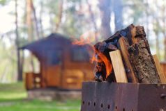 BBQ / Fireplace in the garden. Spring log house in a forest with a BBQ (Grill) Set / Fireplace in front stock image