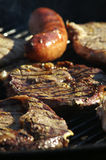 BBQ food. On the grill, shallow depth of field wit focus on the chop in the center Royalty Free Stock Photo