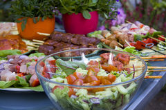 Bbq in the garden. Salad with raw meat on a table in the garden Royalty Free Stock Image