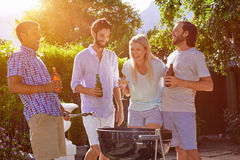 Bbq garden party. Group of friends having outdoor garden barbecue laughing with alcoholic beer drinks stock images