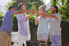 Bbq garden party. Group of friends having outdoor garden barbecue laughing toasting with alcoholic beer drinks stock photos
