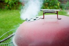 BBQ Grill. Smoking BBQ grill in backyard stock images