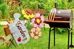 BBQ grillar och ARBETA I TRÄDGÅRDEN undertecknar in trädgården Royaltyfri Bild