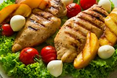 BBQ: grilled chicken breast, tomatoes,peach slices and mini mozzarella on wooden desk Stock Photo