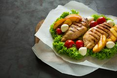 BBQ: grilled chicken breast, tomatoes,peach slices and mini mozzarella on wooden desk Royalty Free Stock Images