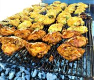 BBQ Grilled Chicken Thighs over Charcoal. With barbecue sauce, on La Caja China stock photo