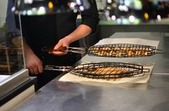 Bbq grilled fish. Cook prepares to serve a bbq grilled fish royalty free stock photography
