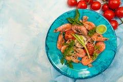 Bbq grilled shrimps on blue plate on blue background  serving wi Stock Images