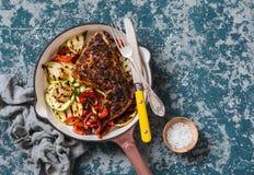 Bbq-höna och grillade grönsaker i en gjutjärnkastrull på en mörk bakgrund, bästa sikt fotografering för bildbyråer