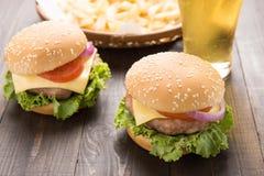 Bbq-hamburgare med fransmansmåfiskar och öl på träbackgrounen Arkivbild