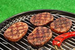 BBQ Hamburger Patties And Chili Pepper On The Hot Grill. Close-up Of BBQ Hamburger Patties And Chili Pepper On The Hot Charcoal Grill. Vibrant Backyard Lawn In Royalty Free Stock Images