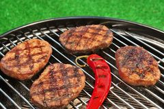 BBQ Hamburger Patties And Chili Pepper On The Hot Grill. Close-up Of BBQ Hamburger Patties And Chili Pepper On The Hot Charcoal Grill. Vibrant Backyard Lawn In Royalty Free Stock Image