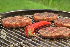 BBQ Hamburger Patties And Chili Pepper On The Hot Grill Royalty Free Stock Photo