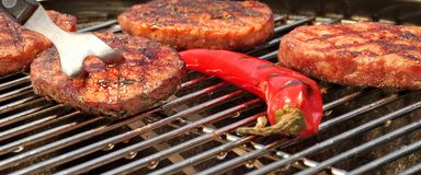 BBQ Hamburger Patties And Chili Pepper On The Hot Grill Stock Photo