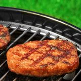 BBQ Hamburger Patties On The Hot Charcoal Grill. Close-up Of BBQ Hamburger Patties On The Hot Portable Charcoal Grill. Backyard Grass In The Background. Cookout Royalty Free Stock Photos