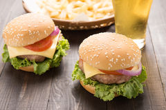 Bbq hamburger z francuza piwem na drewnianym backgroun i dłoniakami Fotografia Stock