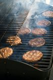 BBQ Hamburgers with smoke. A classic American summer tradition, grilling out on the BBQ with Hamburgers royalty free stock image