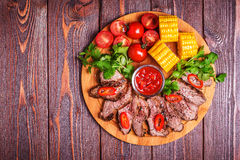 BBQ lamb steak with vegetable and herb on dark wooden background Stock Photo