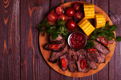 BBQ lamb steak with vegetable and herb on dark wooden background Royalty Free Stock Photo