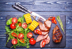 BBQ lamb steak with vegetable salad and corn on dark wooden back Royalty Free Stock Images